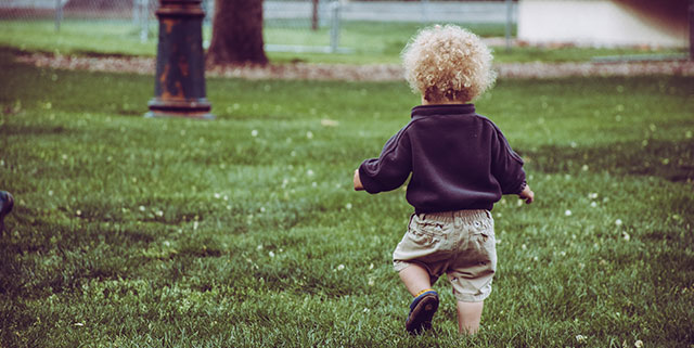 young child running on grass